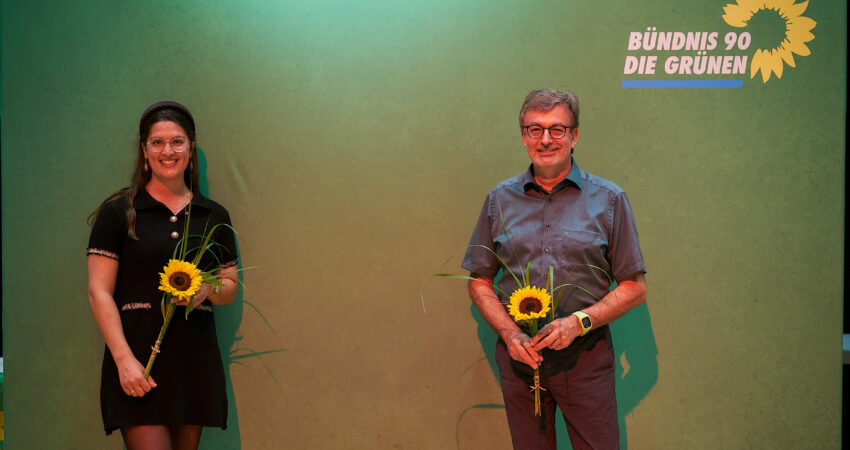 Das Bild zeigt Annika Hummel und Hans-Peter Behrens nach ihrer Nominierung vor einem grünen Hintergrund mit dem Parteilogo und Sonnenblumen in der Hand