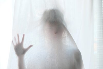 Mensch hinter Vorhand am Fenster